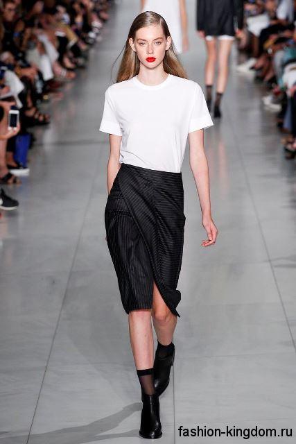 Летняя белая блузка с короткими рукавами сочетается с черной юбкой до колен и кожаными черными туфлями от DKNY.