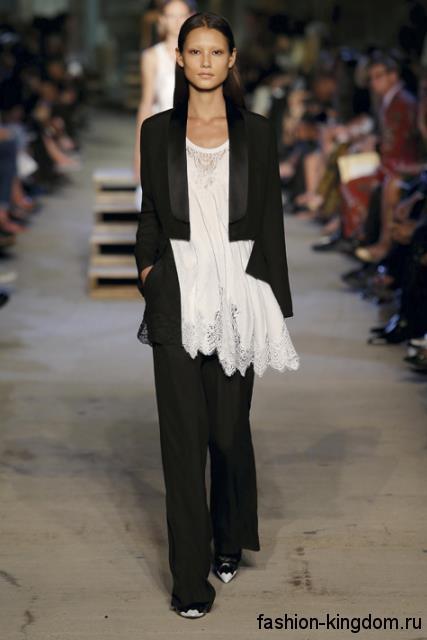 Длинная белая блузка свободного покроя, с ажурными вставками в сочетании с черным брючным костюмом из коллекции Givenchy.