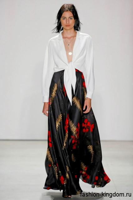 Атласная юбка макси черного цвета с абстрактным рисунком, свободного кроя сочетается с белой блузкой от Jenny Packham.