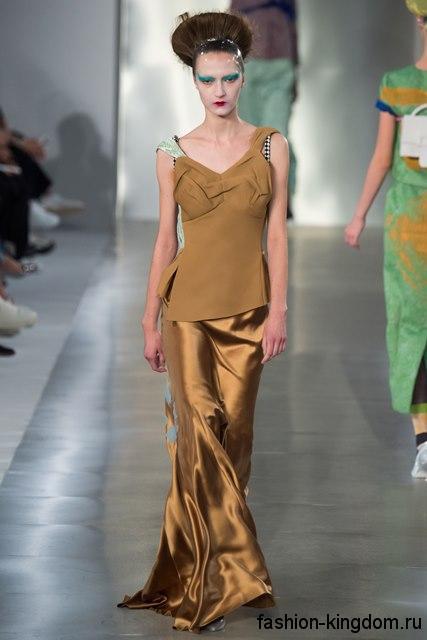 Атласная юбка макси золотистого цвета, с небольшим шлейфом сочетается с блузкой асимметричного кроя от Maison Margiela.