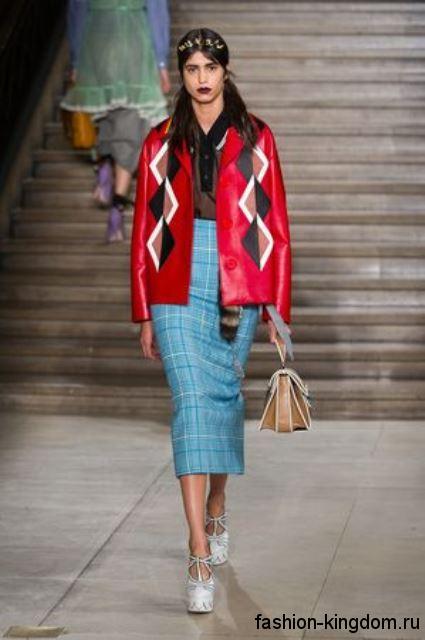 Красная кожаная куртка прямого фасона, с геометрическим рисунком сочетается с голубой юбкой-миди от Miu Miu.
