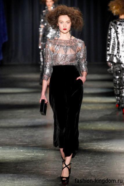 Черная юбка маки зауженного кроя, с завышенной талией в тандеме с шифоновой серебристой блузкой от Naeem Khan.
