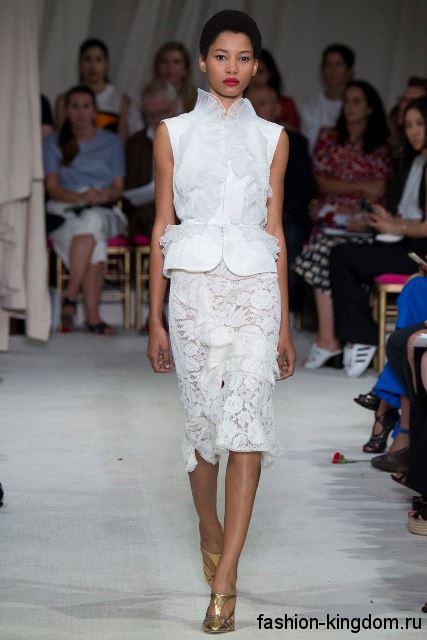 Белая блузка без рукавов, средней длины, с рюшами в тандеме с ажурной белой юбкой до колен из коллекции Oscar de la Renta.