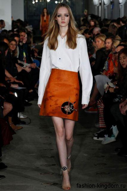 Классическая белая блузка с длинными рукавами дополняется короткой юбкой морковного оттенка от Thomas Tait.