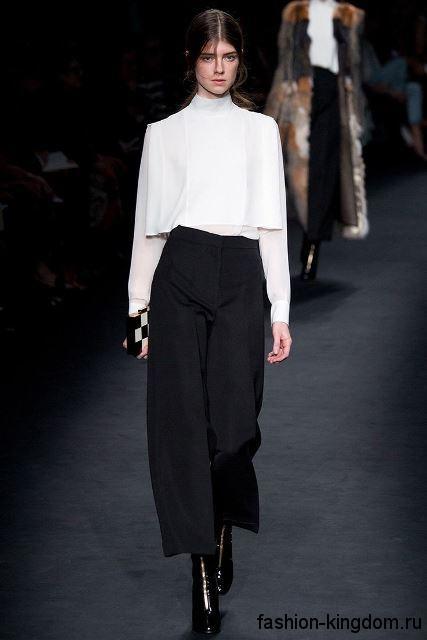 Шифоновая белая блузка с длинными рукавами, свободного силуэта в сочетании с укороченными черными брюками от Valentino.