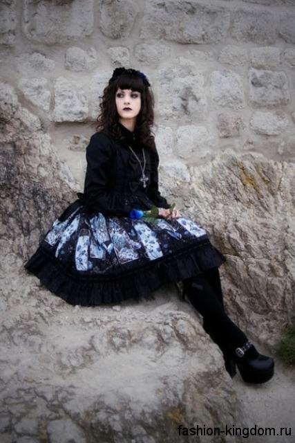 Пышная юбка черно-голубой расцветки с принтом в готическом стиле в сочетании с черной блузой, серебристыми украшениями и туфлями на каблуке.