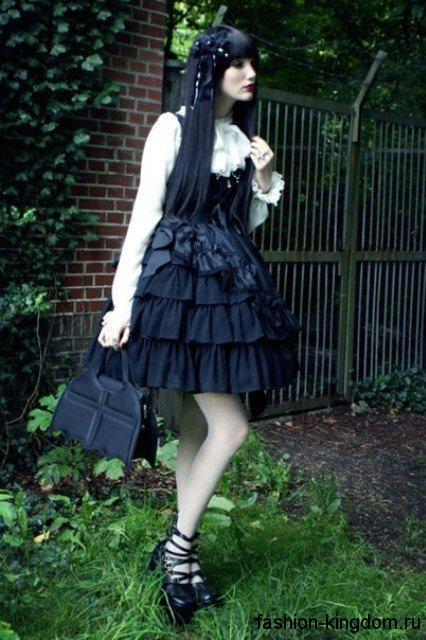 Короткое пышное платье черного цвета с корсетным верхом в готическом стиле в тандеме с белой блузой и тематическими аксессуарами.