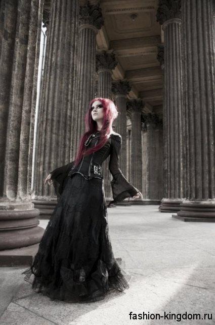 Длинная шифоновая юбка черного цвета в готическом стиле в сочетании с корсетом и тонкой блузкой черного тона с длинными рукавами.