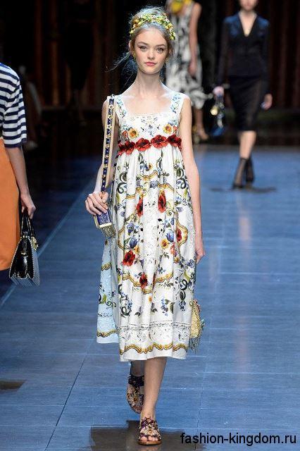 Летнее платье свободного фасона длиной ниже колен, белого цвета с принтом и декоративными элементами от Dolce & Gabbana.