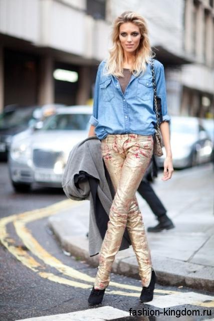 Джинсовая рубашка голубого цвета, свободного фасона в сочетании с узкими блестящими брюками золотистого тона.