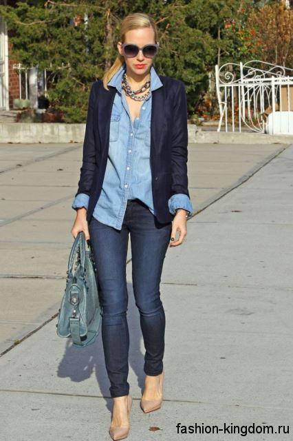 Офисная джинсовая рубашка голубого цвета гармонирует с узкими синими джинсами и темно-синим пиджаком.