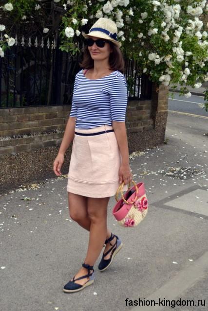 Летняя белая шляпа с синей лентой и узкими полями сочетается с короткой бежевой юбкой и блузкой бело-синего тона в полоску.