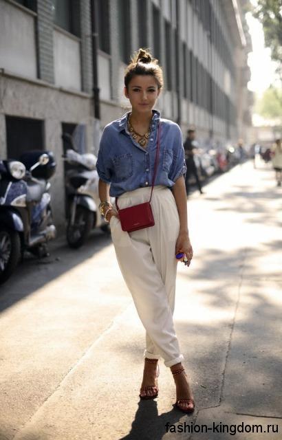 Джинсовая рубашка светло-синего цвета, с накладными карманами в сочетании с белыми брюками свободного кроя.