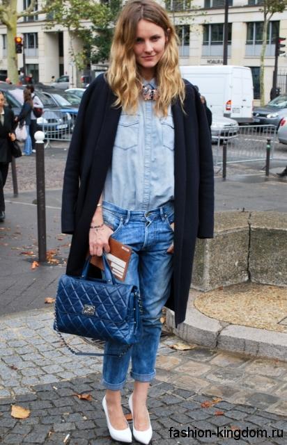 Голубая джинсовая рубашка свободного кроя в сочетании с короткими джинсами и демисезонным пальто.