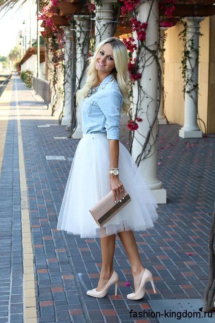 Голубая джинсовая рубашка приталенного кроя гармонирует с пышной юбкой-миди белого цвета и туфлями на каблуке.