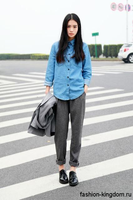 Модная джинсовая рубашка светло-синего цвета в офис в тандеме с брюками серого тона и туфлями на низком ходу.
