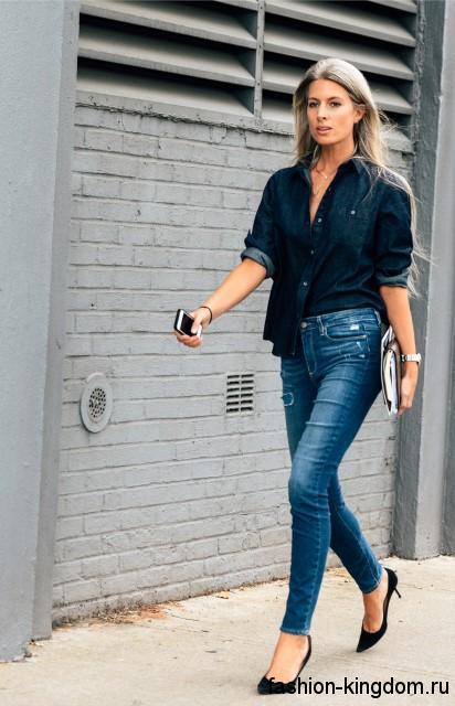 Джинсовая рубашка темно-синего цвета, свободного кроя, с длинными рукавами в тандеме с узкими синими джинсами.