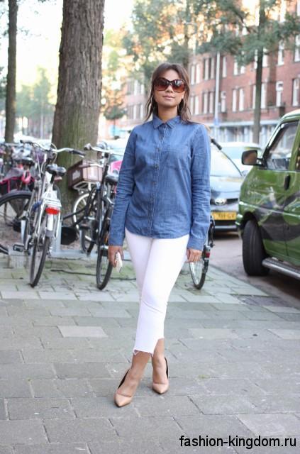 Классическая джинсовая рубашка синего цвета, с длинными рукавами сочетается с укороченными белыми брюками.