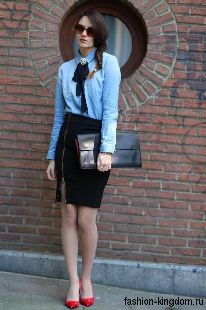 Джинсовая голубая рубашка с длинными рукавами для работы сочетается с черной юбкой-карандаш и туфлями на каблуке.