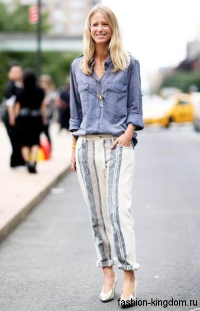 Женская джинсовая рубашка серо-синего цвета, свободного фасона, с длинными рукавами сочетается со светло-серыми брюками.
