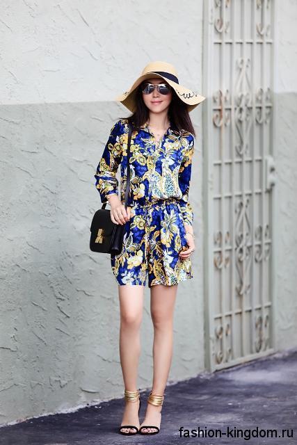 Широкополая летняя шляпа с черной ленточкой дополняет короткое платье сине-желтой расцветки.
