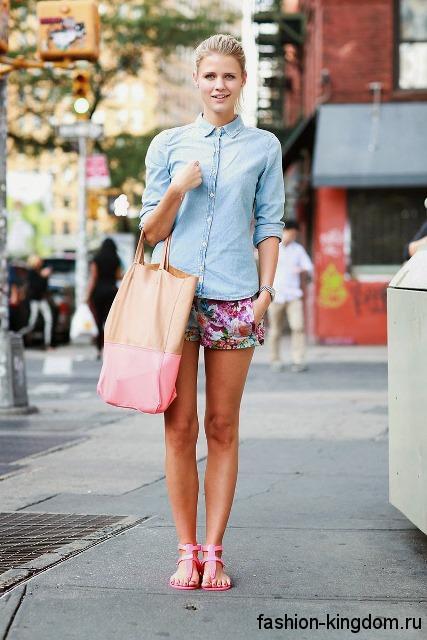 Джинсовая рубашка светло-голубого цвета, приталенного фасона дополняется короткими шортами с цветочным принтом.
