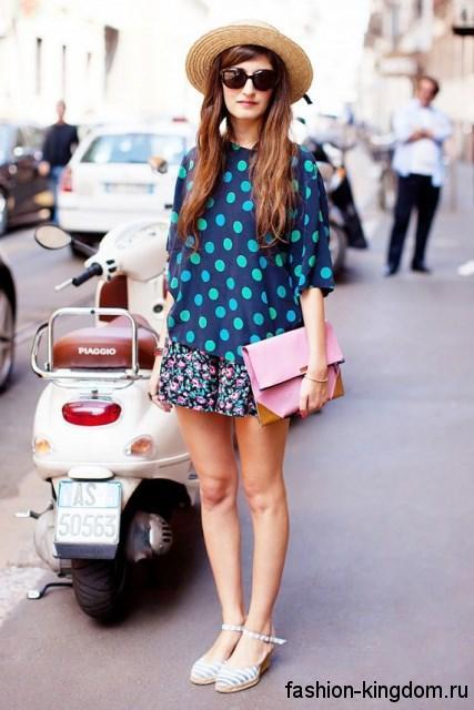 Соломенная летняя шляпа удачно смотрится с блузой синего тона в горошек и юбкой-мини с цветочным принтом.