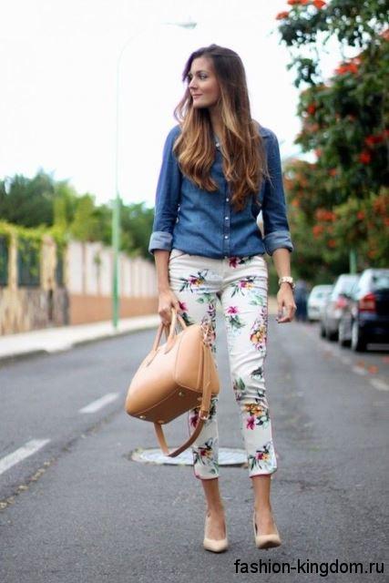 Джинсовая рубашка синего цвета с длинными рукавами в тандеме с короткими белыми брюками с цветочным принтом.