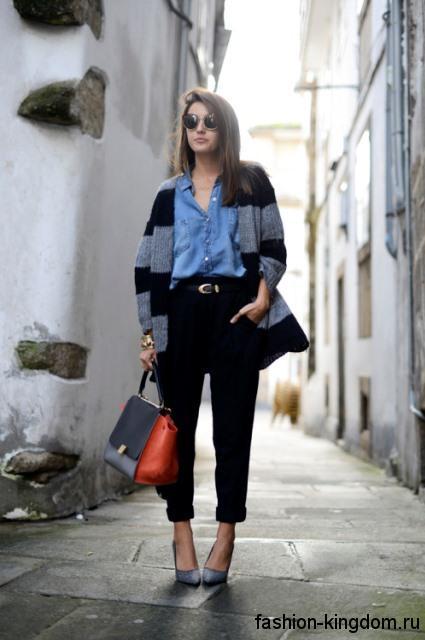 Джинсовая рубашка голубого цвета, свободного фасона сочетается с черными брюками и длинным кардиганом.