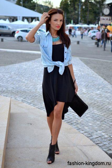 Короткая джинсовая рубашка голубого цвета сочетается с коротким черным платьем и ботильонами на каблуке.