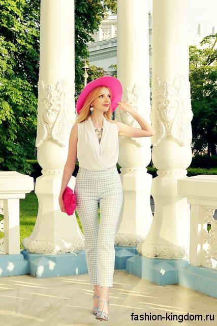 Летняя шляпа розового цвета с широкими полями дополнит белую блузу и укороченные белые брюки.