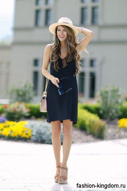 Летняя шляпа бежевого цвета с широкими полями сочетается с коротким платьем черного тона.