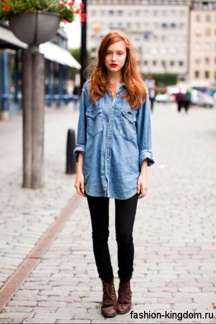 Длинная джинсовая рубашка синего цвета, свободного фасона в сочетании с узкими черными брюками.