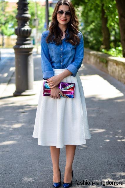 Летняя джинсовая рубашка светло-синего цвета гармонирует с юбкой-миди белого тона и черными туфлями на каблуке.