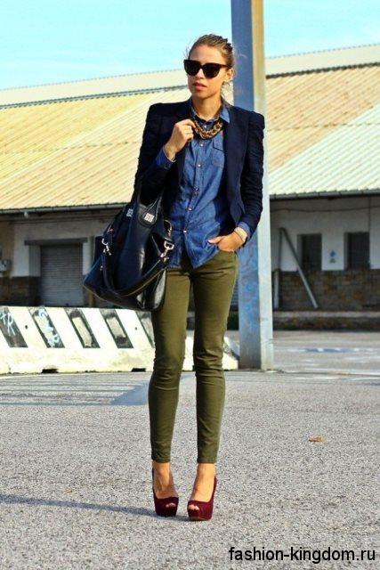 Джинсовая рубашка синего цвета, приталенного фасона сочетается с узкими брюками зеленого оттенка.
