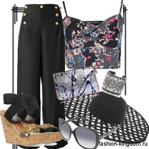 Черная летняя шляпа с широкими ажурными полями в тандеме с широкими черными брюками и коротким топом.