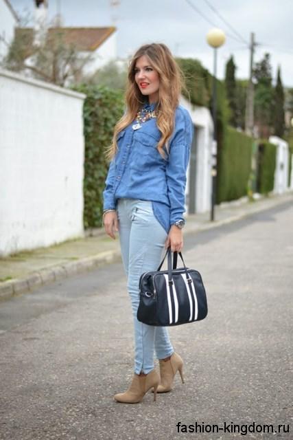 Длинная джинсовая рубашка светло-синего цвета, свободного кроя в сочетании с узкими джинсами голубого тона.