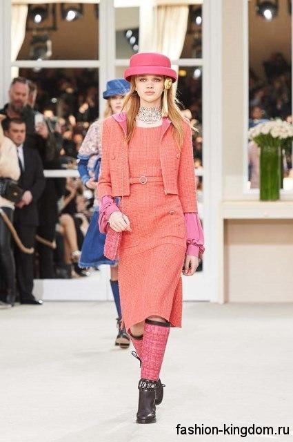 Летняя шляпа розового цвета с узкими полями сочетатеся с платьем-миди и жакетом кораллового тона от Chanel.