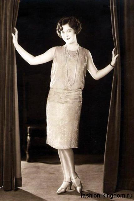 Модное платье 1920 годов прямого кроя, длиной миди, без рукавов в сочетании с ниткой жемчуга и туфлями на низком каблуке.