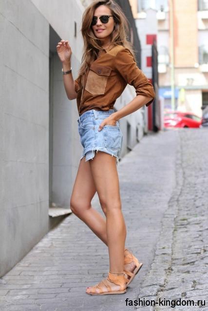 Модные босоножки на плоской подошве, бежевого цвета сочетается с джинсовыми шортами и коричневой рубашкой.