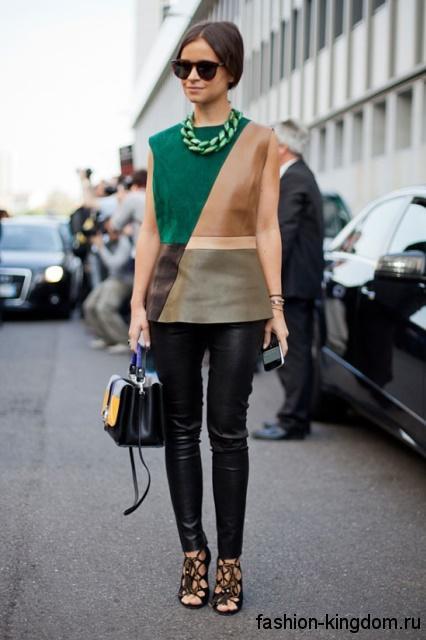 Черные босоножки на каблуке со шнурками сочетаются с кожаными брюками и блузой без рукавов.