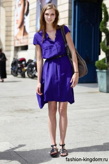 Черные босоножки на низком ходу, с ремешками дополняют короткое платье синего цвета.