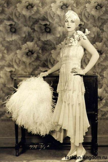 Длинное платье 1920 годов прямого силуэта, с драпировкой сочетается с жемчужными украшениями и туфлями на каблуке.