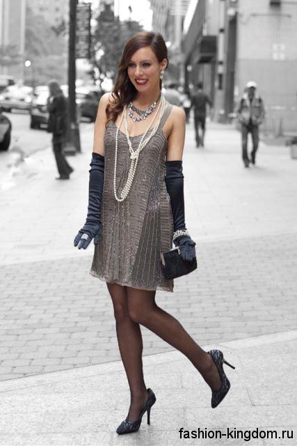 Короткое платье прямого кроя в стиле 1920, серебристого цвета, на бретельках в сочетании с жемчужными украшениями.