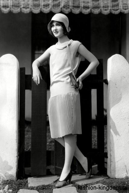 Летнее платье 1920 годов прямого покроя, длиной чуть ниже колен, с заниженной талией и без рукавов.
