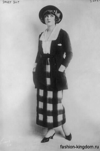 Длинная юбка в клетку 1920 годов прямого кроя в сочетании с белой блузой и длинным темным кардиганом.
