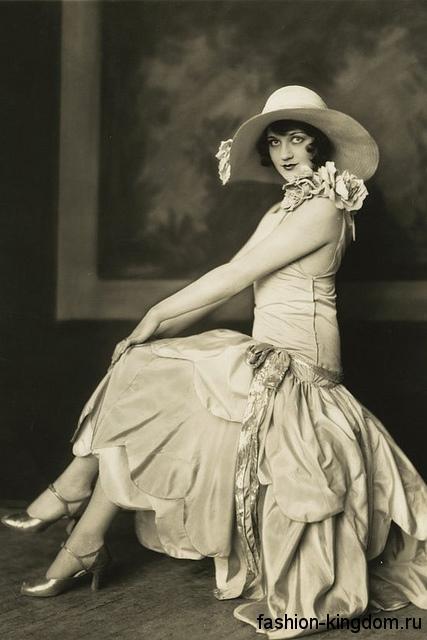 Длинное платье 1920 годов с заниженной талией, украшенное цветами, сочетается с широкополой шляпой и туфлями на каблуке.