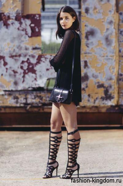 Черные босоножки на высоком каблуке, с ремешками до колен в сочетании с черным платьем-мини.