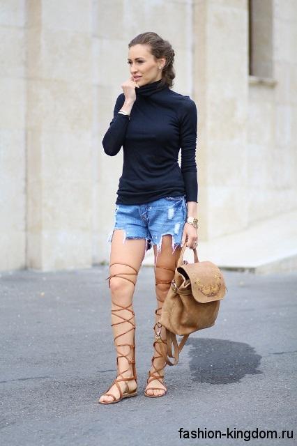 Коричневые босоножки на плоской подошве, с ремешками до колен в сочетании с рваными джинсовыми шортами.