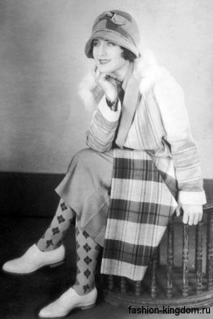 Длинное пальто в клетку 1920 годов, прямого кроя, с меховым воротником в тандеме со шляпой клош и туфлями в мужском стиле.
